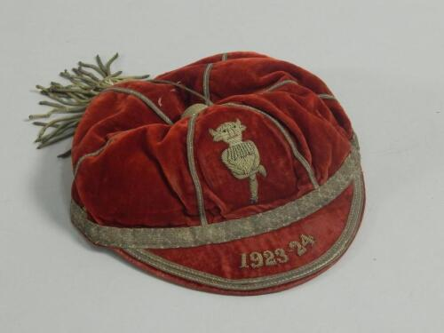 A red velvet and white metal sporting cap