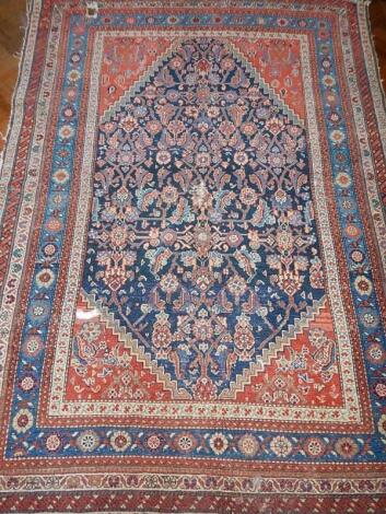 A 19thC Persian bordered rug in blue and red