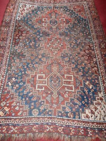 A 19thC Persian bordered rug in red and blue