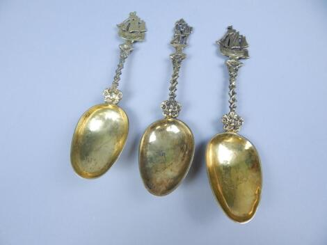 A set of three continental gilt white metal commemorative type spoons