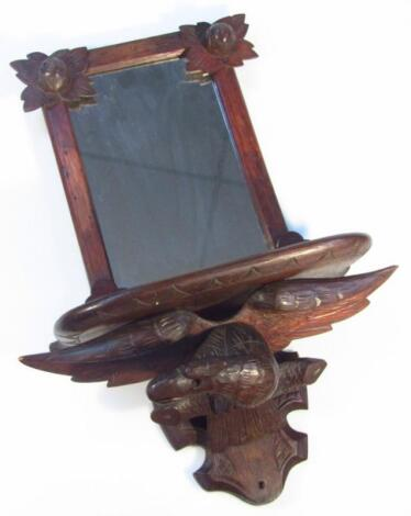 An early 20thC oak stained hardwood Black Forest style wall shelf and mirror
