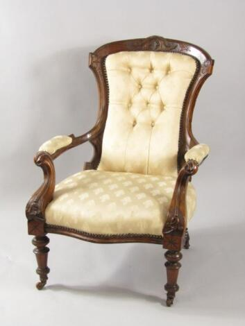 A Victorian mahogany armchair with carved crest rail