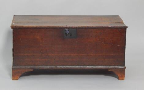 An 18thC oak coffer raised on bracket feet