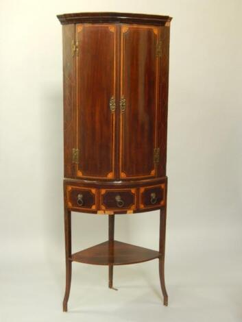 A George III mahogany and satinwood inlaid bow front corner cupboard on stand