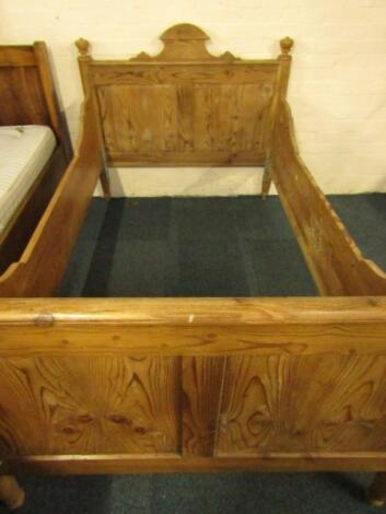A pine single bed with carved headboard