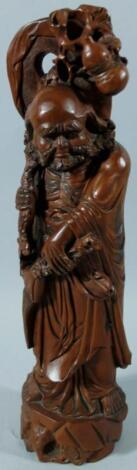 A heavily carved Chinese hardwood figure of a bearded sage