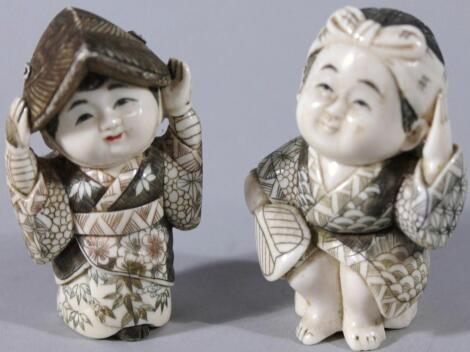 A pair of Japanese Fukusuke good fortune figures
