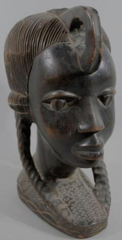 A 20thC heavily carved ebony African tribal figural head