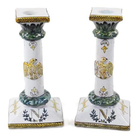A pair of 19thC faience tin glazed earthenware pottery Napoleonic candlesticks