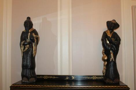 A pair of reproduction carved oriental figures