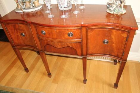 A reproduction Sheraton serpentine sideboard
