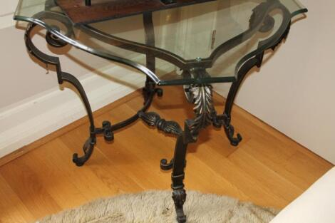 A glass and wrought iron framed occasional table