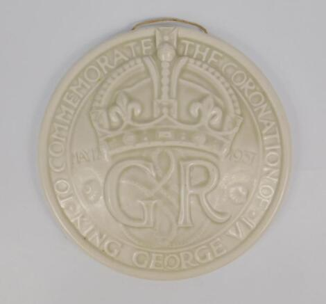 An ivory monochrome pottery circular wall plaque to commemorate The Coronation of King George VI