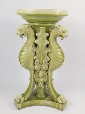 A Victorian late 19thC pottery green glazed jardiniere stand
