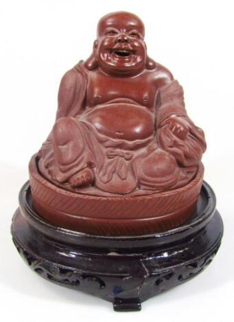A large red stoneware style Buddha