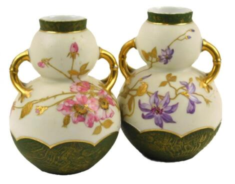 A pair of Continental porcelain two handled double gauge shaped vases