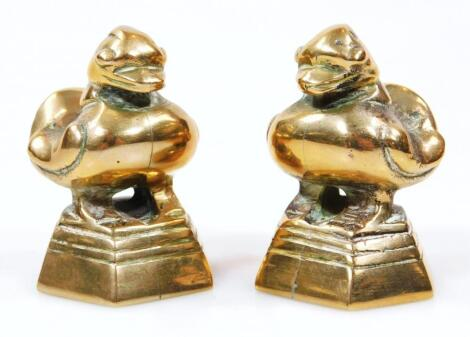 A pair of polished bronzed desk seals