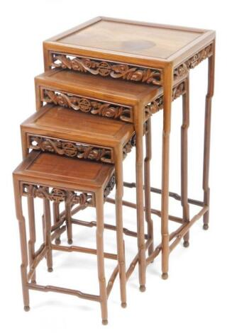 A nest of four Chinese carved wooden tables