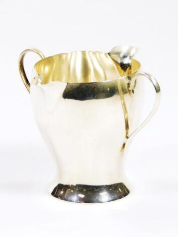 A Victorian Art Nouveau silver double lipped cream jug
