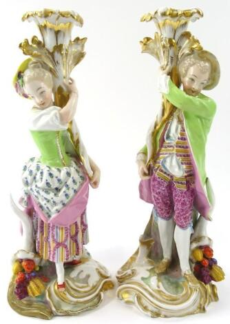 A pair of Continental figures of a lady and gentleman candle holders