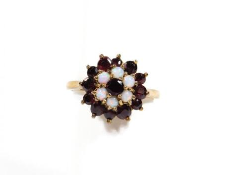 An early 20thC ladies garnet and opal dress ring