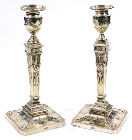 A pair of silver plated Adam design Neo-Classical candlesticks