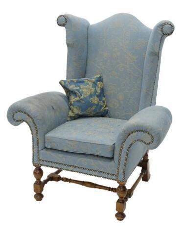 An unusual walnut wingback armchair