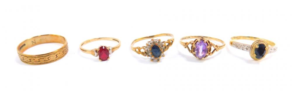Four 9ct gold and gem set rings, sizes J - O, and a 9ct gold wedding band...