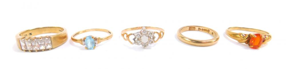 Four 9ct gold and gem set rings, sizes O-U, and a 9ct gold wedding band...