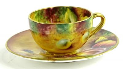 A Royal Worcester porcelain cup and saucer, painted with fruit by T Knott, printed mark in black to underside.