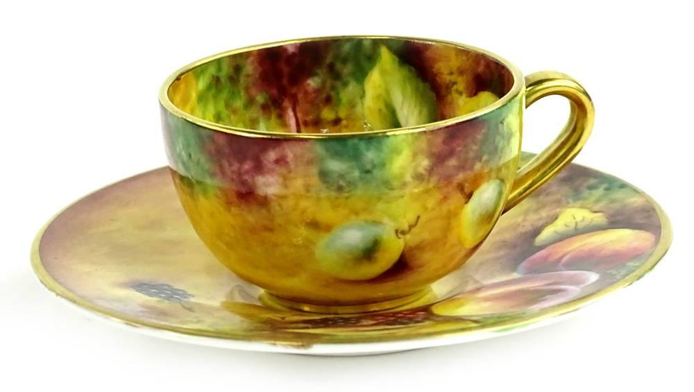 A Royal Worcester porcelain cup and saucer, painted with fruit by T Knott...