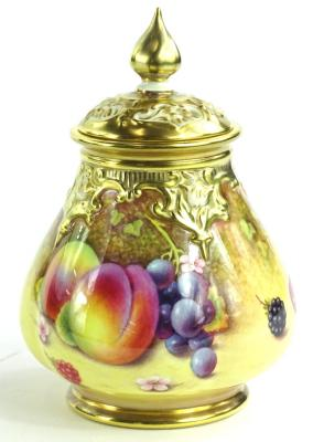 A Royal Worcester porcelain vase and cover, with a pierced lid, the base decorated with fruit by P Platt, printed mark in black to underside, numbered H291A, 13cm H.