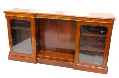 A Victorian walnut and marquetry inverted break front bookcase, the top with a moulded edge above a frieze decorated with ribbons, foliate scrolls etc., above two glazed doors, flanking a central open shelved area on plinth base, 103cm H, 199cm W. Provenance: The property of Joan Stephenson, Kirkwood, North Church Walk, Newark, Nottinghamshire.