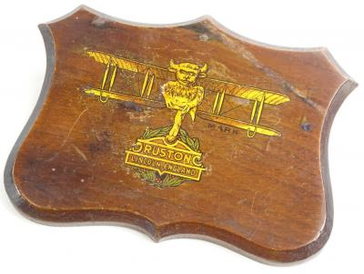 An early 20thC mahogany plaque, decorated with a transfer print of a gilt bi plane and the crest of the Ruston factory of Lincoln, England, (AF), 12cm x 9cm.