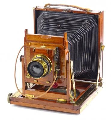 A Thornton Pickard mahogany and brass plate camera, with canvas bellows, the lens stamped Beck Symmetrical, 26cm L when opened.
