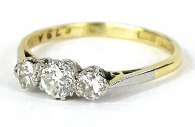 A three stone diamond ring, set with three round brilliant cut diamonds, in claw setting, with pierced ring head, set in platinum on a yellow metal band, ring size P½, 2.5g all in.
