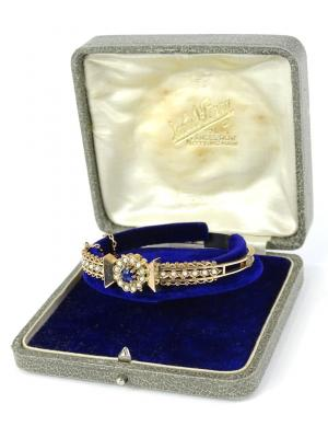 An Edwardian hinged bangle, set with central cluster of sapphire surrounded by seed pearls, with fine ball and wire design, and seed pearl set shoulders, yellow metal, unmarked, with safety chain, 6cm wide.