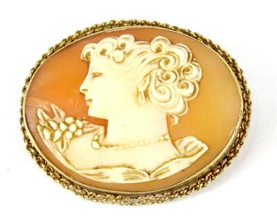 A shell cameo brooch, of maiden head and shoulders, of oval form, in yellow metal frame, with twist design borders, unmarked, 4.5cm W, 9.4g all in. Provenance: The property of Joan Stephenson, Kirkwood, North Church Walk, Newark, Nottinghamshire.
