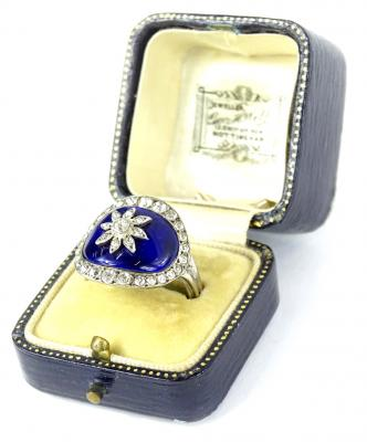A late 19thC/early 20thC dress ring in George III style, with central oval blue enamel panel set with central floral design and paste set flower and borders, silver plated, ring size S½.