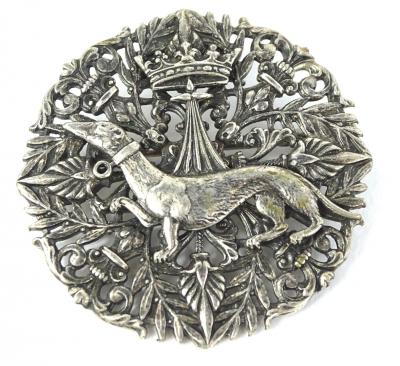 A Cannetille filigree whippet and crown brooch, of circular form with leaves and scrolls and central whippet and crown, unmarked, possibly silver, 4cm diameter.