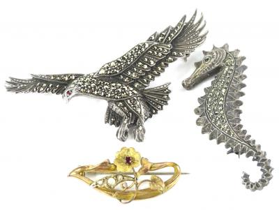 Three brooches, to include a silver and marquasite set eagle brooch, 7cm wide, a silver and marquasite set sea horse, 5.5cm high, and a 9ct gold floral brooch, set with garnet and seed pearl, 3.5cm wide, 2.1g. (3)
