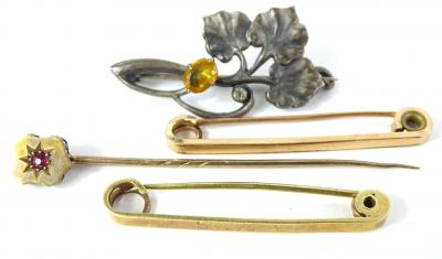 Four brooches and stick pins, to include a silver leaf brooch, 3.5cm wide, a stick pin set with garnet, yellow metal, unmarked, two bar brooches, yellow metal, one marked 15ct, gold 4.5g all in.