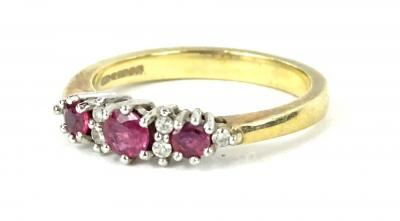 A 9ct gold dress ring, set with three garnets and tiny white stones, each in claw setting, ring size L, 2.9g all in, boxed.
