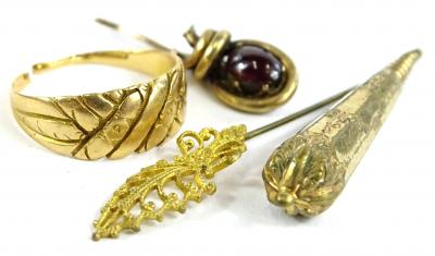 A small quantity of jewellery and trinkets, to include a dress ring, yellow metal, unmarked and cut, 3.8g, two stick pin heads, on set with garnet and a gilt metal earring bit.