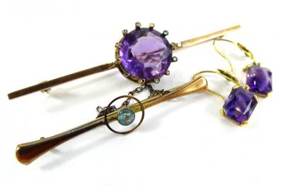 Two bar brooches and a pair of earrings, to include an amethyst and tiny diamond set bar brooch, the central amethyst 1.6cm wide, yellow metal, unmarked, 7cm wide, a pair of associated drop earrings, gold plated and a bar brooch set with central pale blue stone, yellow metal bar brooch, 5cm wide.