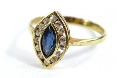 A marquise shaped dress ring, set with central pale blue stone, possibly tanzanite, with tiny diamond borders, each in tension setting, on a yellow metal band, marked 585, ring size P, 2.6g all in.
