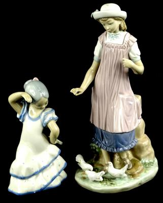 A Lladro porcelain figure, of a lady wearing a purple pinafore, feeding some doves, printed mark in blue to underside, 28cm H, and a Spanish porcelain figure of a dancing girl. (2)