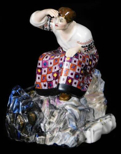 A rare and important Russian porcelain Natalina Danko figure of a female worker, wearing an elaborate dress with a pick and spade at her feet, possibly used as an inkwell, c,1920, signed, 12cm H. (AF)
