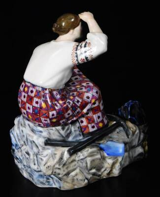A rare and important Russian porcelain Natalina Danko figure of a female worker, wearing an elaborate dress with a pick and spade at her feet, possibly used as an inkwell, c,1920, signed, 12cm H. (AF) - 2