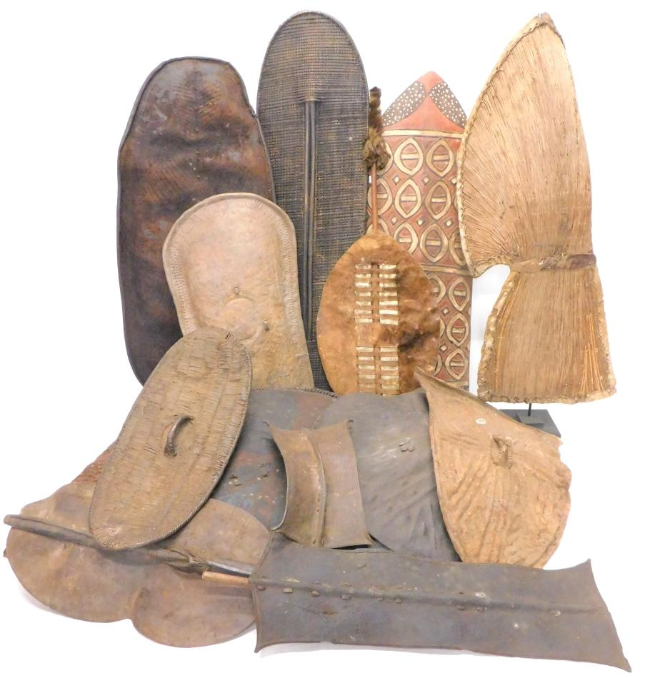 A collection of African leather and carved wooden tribal shields to be...